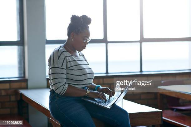 young woman surfing net through laptop on table - black trousers stock pictures, royalty-free photos & images