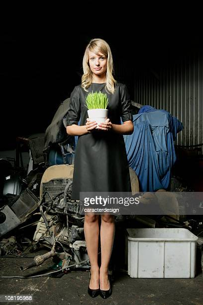 Young Woman Surrounded by Garbage Holding Flower Pot with Grass
