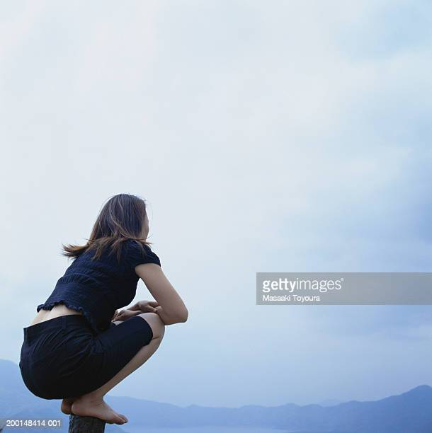 Young woman surrounded by mountains, kneeling on post above water