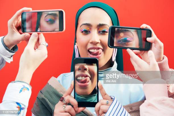 young woman surrounded by smartphones. - photo messaging stock photos and pictures