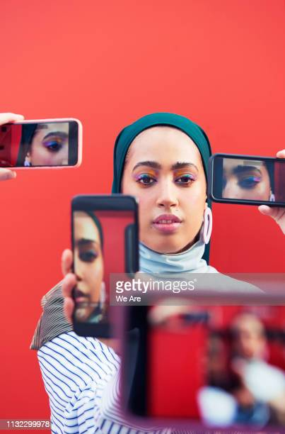 young woman surrounded by smartphones. - street style stock pictures, royalty-free photos & images