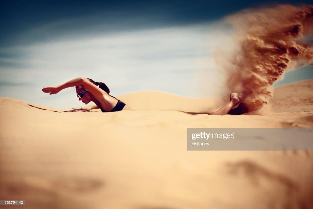 Young woman swim in desert : Stock Photo
