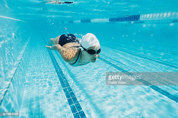 Young Woman Swimming in a Pool Underwater