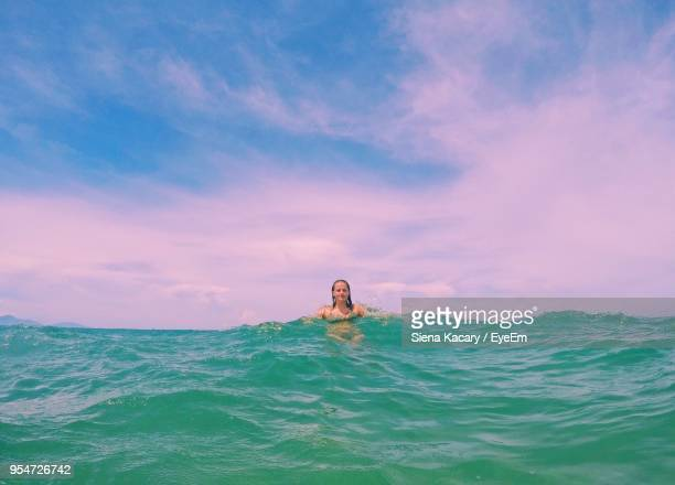 Young Woman Swimming In Infinity Pool Against Sky