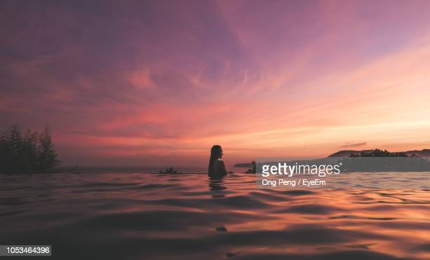 young woman swimming in infinity pool by sea against sky during sunset - infinity pool foto e immagini stock