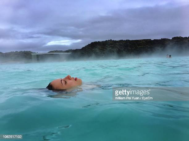 young woman swimming in pool - blue lagoon iceland stock pictures, royalty-free photos & images