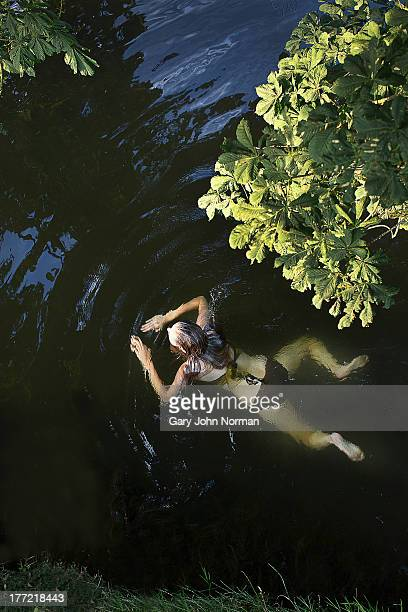 young woman swimming in river - river stock pictures, royalty-free photos & images