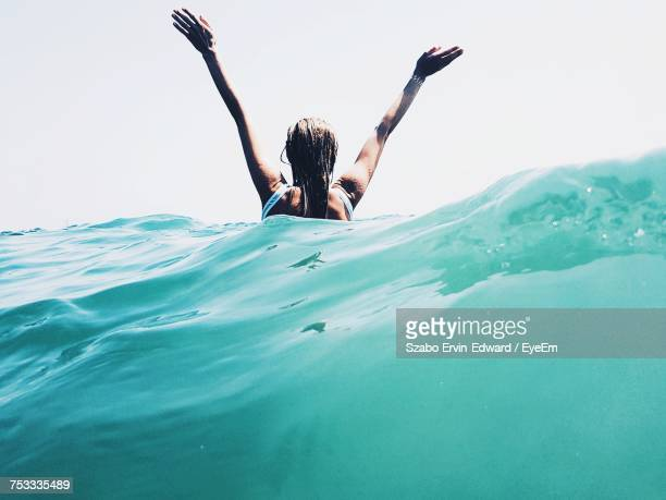 young woman swimming in sea - arms outstretched stock pictures, royalty-free photos & images