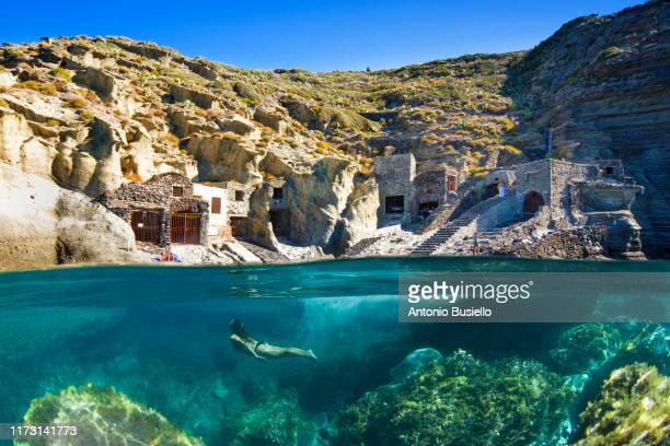 young woman swimming underwater with pollara old fishing boat shed in surface - isola di salina sicilia foto e immagini stock
