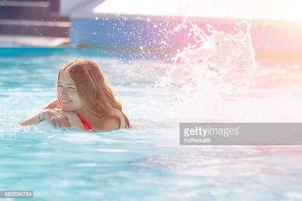 Junge Frau mit einem beach-ball am Swimmingpool