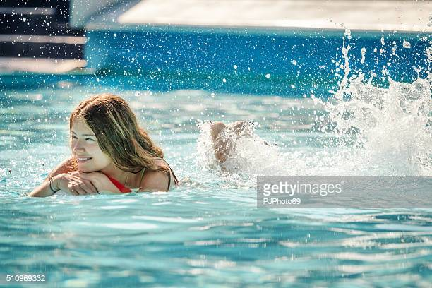 Young woman swimming with beach ball on swimming pool
