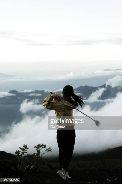 young woman swing golf on mt.fuji - 選手  ストックフォトと画像