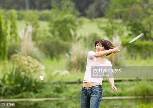 Young woman swinging badminton racket
