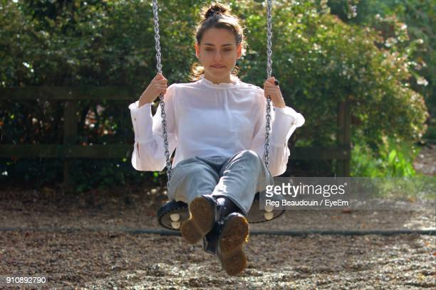 Young Woman Swinging During Sunny Day