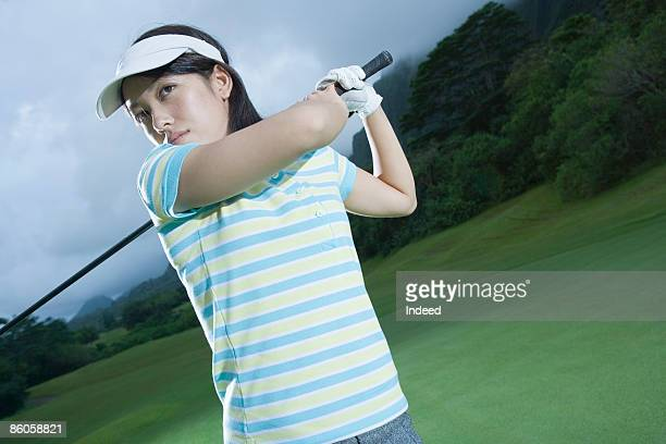 Young woman swinging golf club on green