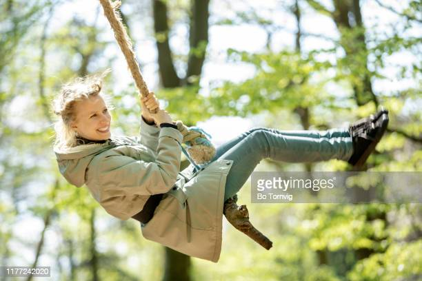 young woman swinging in the forest - bo tornvig stock pictures, royalty-free photos & images