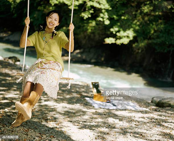 Young Woman Swinging on a Rope Swing