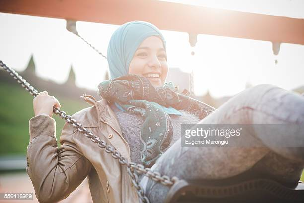 Young woman swinging on playground swing