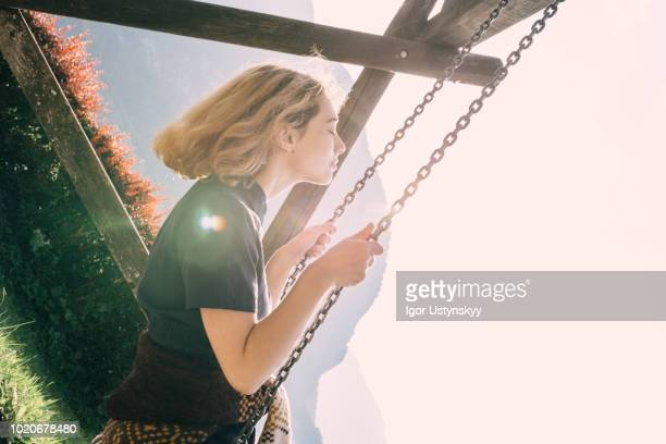 young woman swinging on swing - traumhaft stock-fotos und bilder