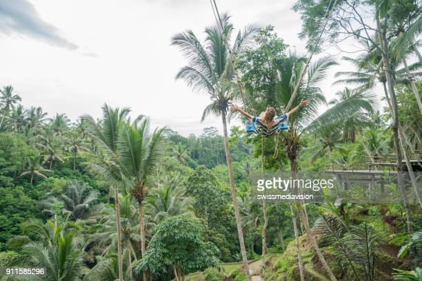Young woman swinging over the jungle, Bali