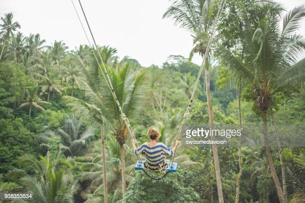 young woman swinging over the jungle, bali - ubud district stock pictures, royalty-free photos & images