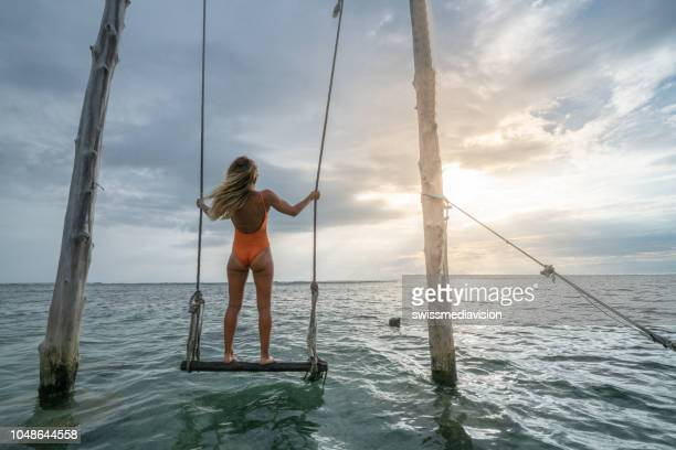 mujer joven que hace pivotar sobre el mar, hermosa y paisaje idílico. personas viajan concepto de vacaciones. - lombok fotografías e imágenes de stock