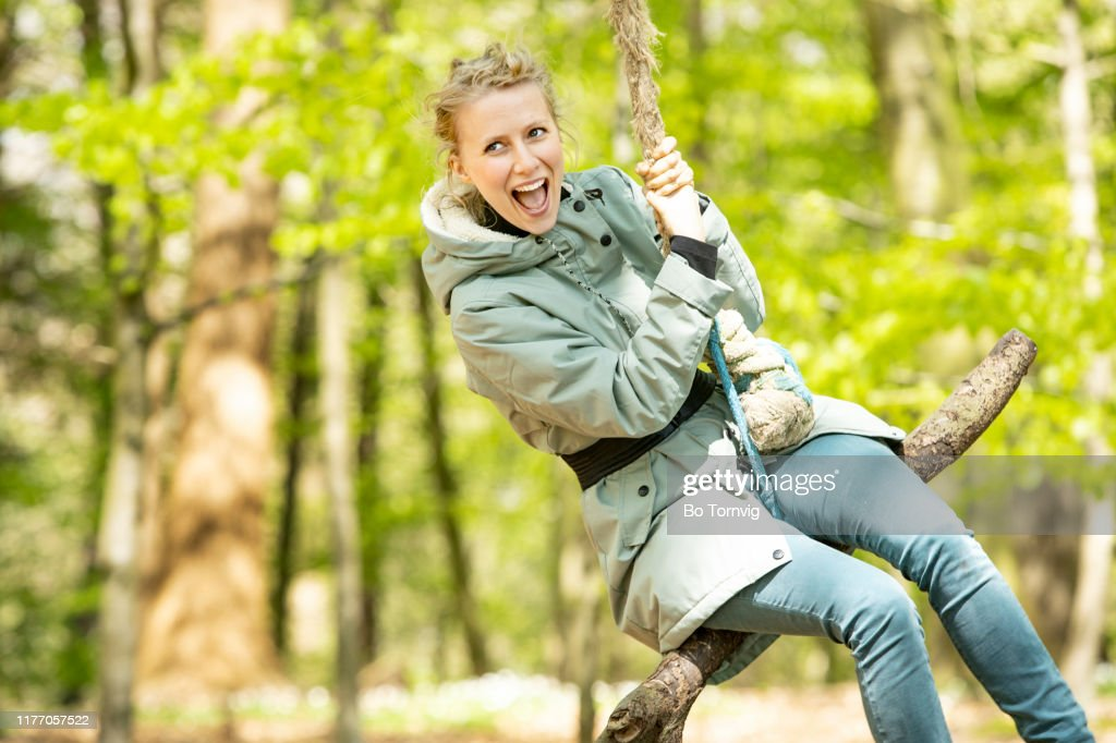 young woman swings in the forest : Stock Photo