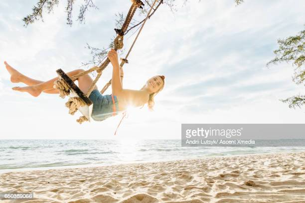 Young woman swings on beach chair, above sea