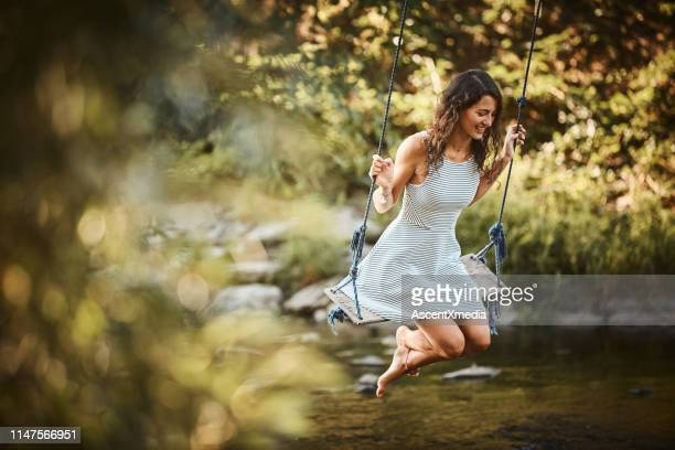 young woman swings over stream - swing stock pictures, royalty-free photos & images