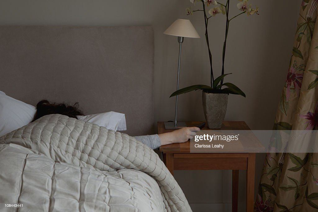 Young woman switching off phone alarm : Stock Photo