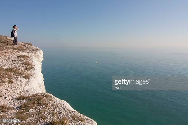 A Young Woman Take a Picture of Magnificent Seaside Landscape on a White Cliff with Blue Sky