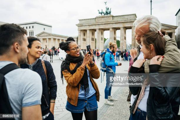 a young woman take photo of friends at brandenburg gate in berlin - incidental people stock pictures, royalty-free photos & images