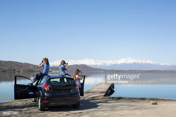 young woman take pictures from car, at lake - jetty stock pictures, royalty-free photos & images