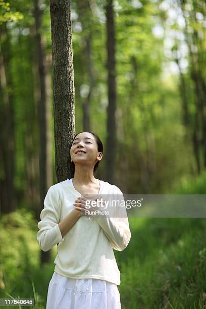 young woman takes a deep breathin the forest