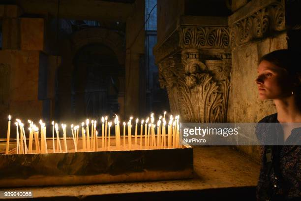 A young woman takes a moment to contemplate at the site of Golgotha inside the Holy Sepulchre church in the Old Town of Jerusalem Wednesday 14 March...