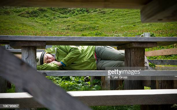A young woman takes a nap on a bench after a long hike and filling lunch in the Swiss Alps.