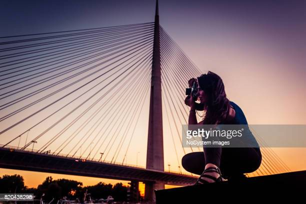 Young woman takes a photograph with a retro film camera on sunset