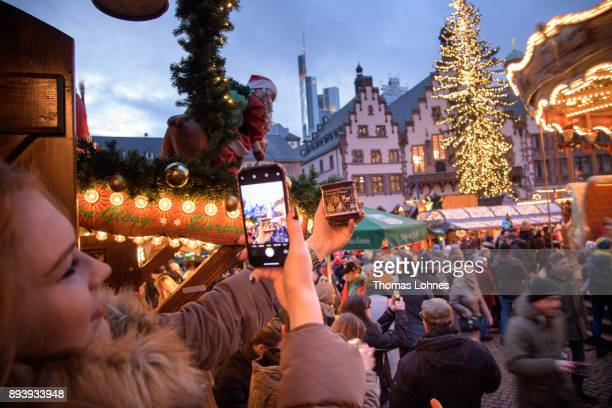 A young woman takes a picture of Christmas market cup at the annual Christmas market at Roemerberg on December 16 2017 in Frankfurt Germany Christmas...
