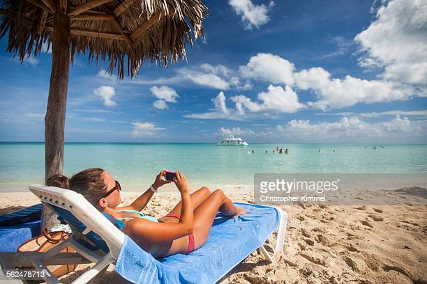 A young woman takes a picture with her smartphone while relaxing on the beach