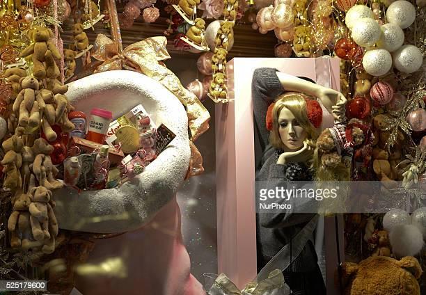 Young woman takes a selfie near Brown Thomas' Christmas window decoration on Grafton street, Dublin, Ireland.