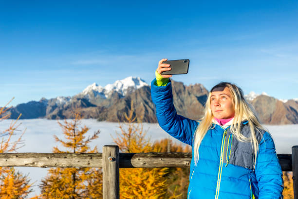 Young woman takes a selfie photo with smartphone.