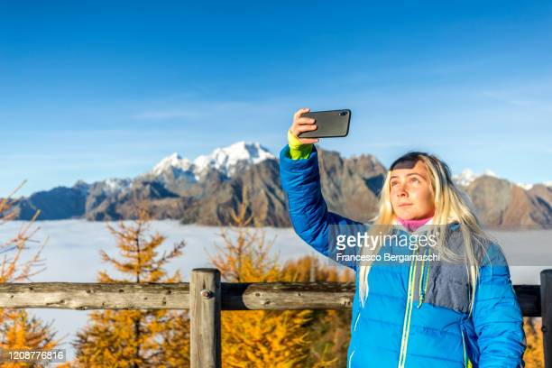 young woman takes a selfie photo with smartphone. - italia ストックフォトと画像