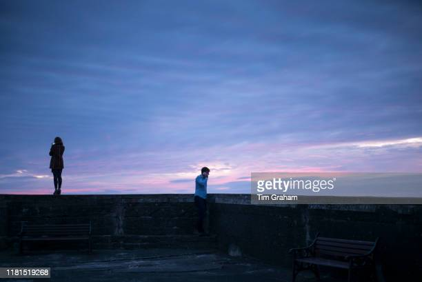 Young woman takes a smartphone photograph of pastel colours of setting sun while her partner takes a phone call on his smartphone Wales United Kingdom
