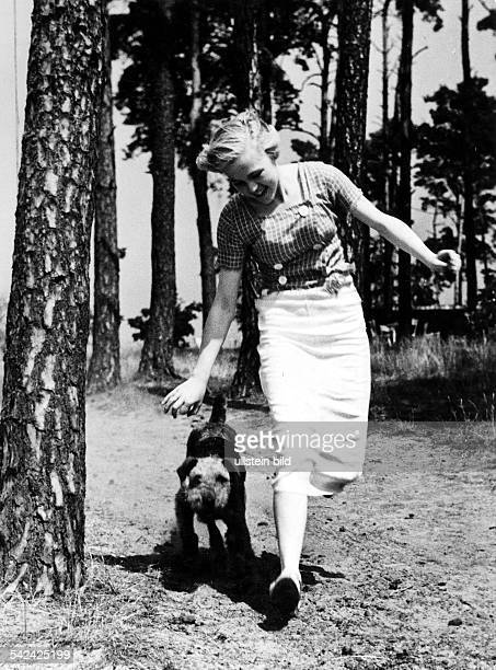 young woman takes a walk with her Airedale terrier in a pine forest picture taken by Heinz von Perkhammer 1938