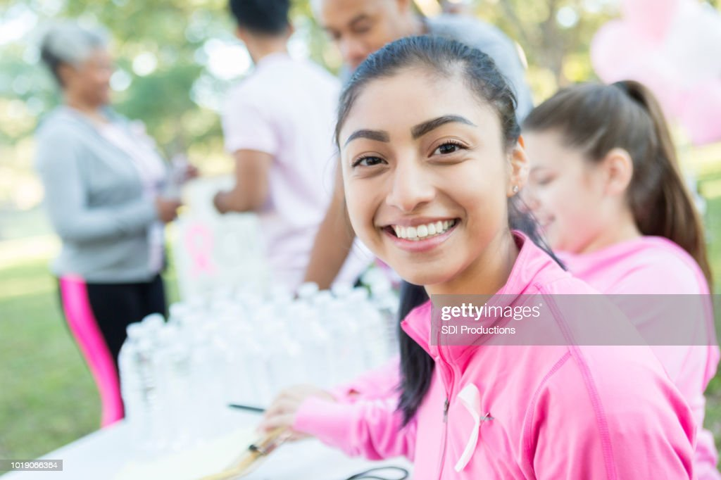 Young woman takes a water break during charity race : Stock Photo