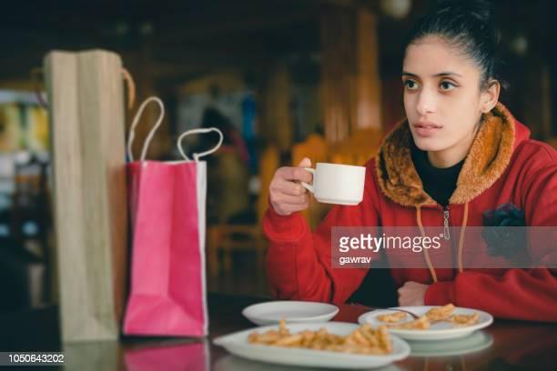 若い女性は、買い物の後、レストランでコーヒー休憩を取る. - 南アジア ストックフォトと画像