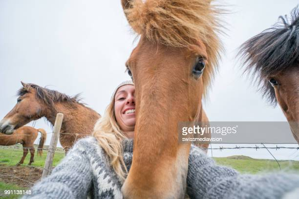 Young woman takes fun selfie portrait with Icelandic horse in meadow