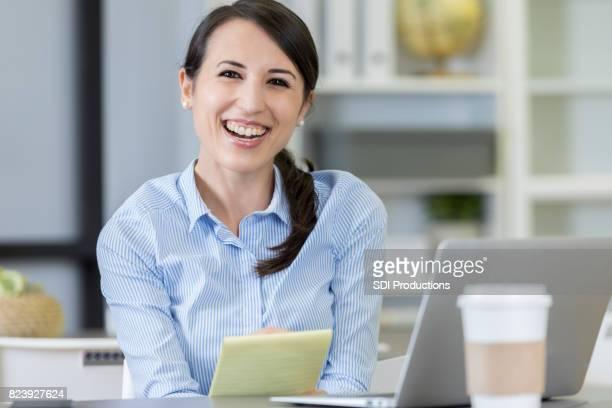 若い女性は、カメラに向かって微笑んでノート