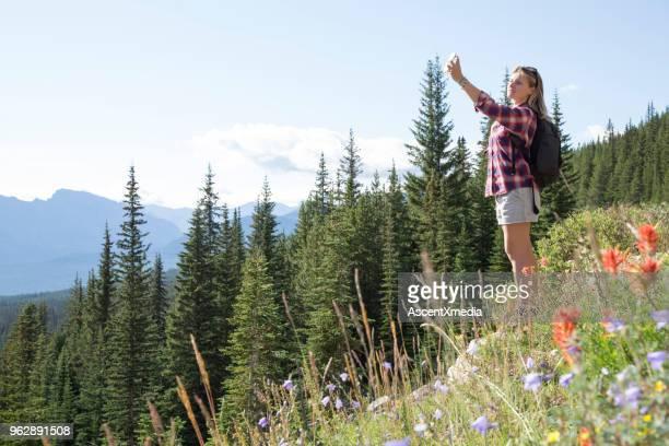 Junge Frau nimmt Foto an Wildblumen mit Handy
