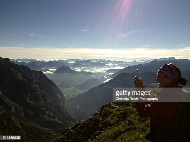 Young woman takes photos in the Bavarian Alps